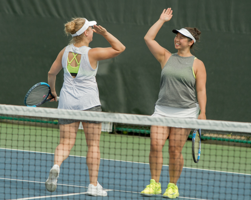 two girls playing tennis about to high five
