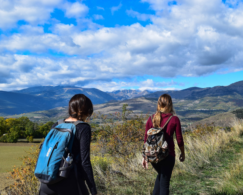 two girls hiking with blue sky and mountains