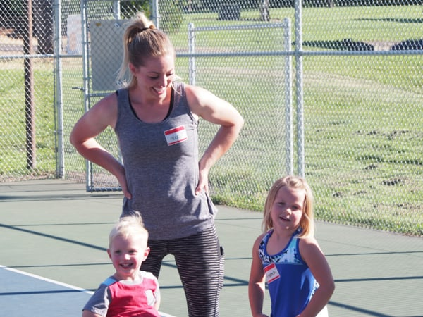 Mom and small children having fun and laughing outside. playing tennis.