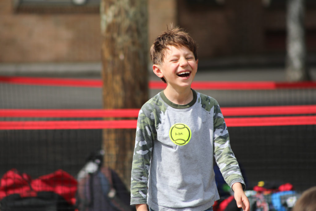 child laughing tennis court